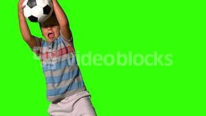 Little boy catching football on green screen