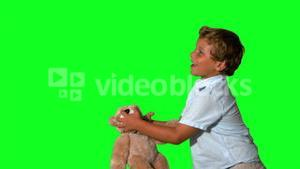 Little boy jumping and catching teddy on green screen