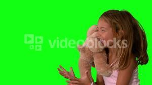 Cute little girl catching teddy bear on green screen and jumping