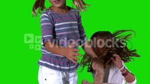 Sisters jumping on green screen with teddy