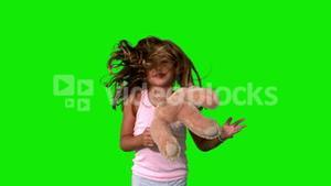 Little girl jumping up and turning with teddy on green screen