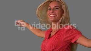 Attractive blonde jumping on grey background