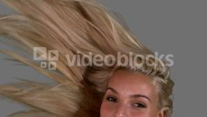Attractive blonde tossing her hair up on grey background close up