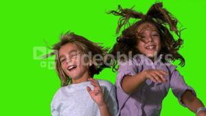 Brother and sister jumping up and crashing on green screen