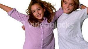 Brother and sister jumping into same shot and embracing on white background