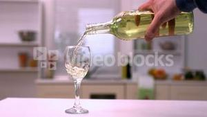 Hand pouring white wine into glass