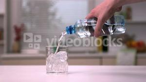 Hand pouring water into a glass with ice cubes