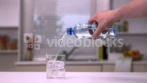 Hand pouring water into a glass