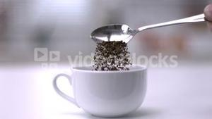 Pouring instant coffee off teaspoon into a white cup