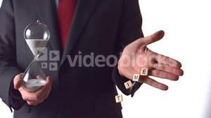 Man holding an hourglass and dropping letter pieces spelling time