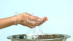Woman washing her hands under stream of water in a sink