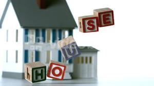 Blocks spelling house falling over in front of a miniature house