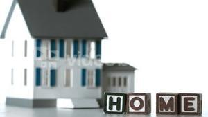 Blocks spelling home sliding along in front of a miniature house