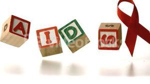 Blocks spelling Aids dropping down in front of a red ribbon