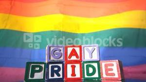 Rainbow flag moving in the breeze with gay pride blocks in front