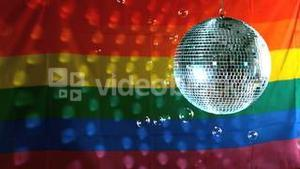 Shiny disco ball turning with floating bubbles against rainbow flag