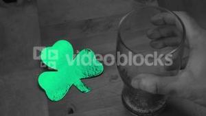 Hand putting down empty pint beside large green shamrock