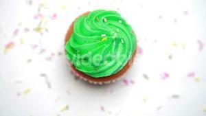 St patricks day cupcake turning with sprinkles falling