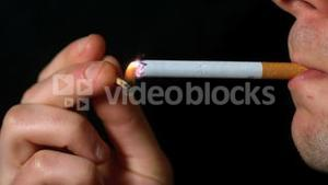 Man lighting up cigarette with match