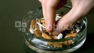 Hand putting cigarette out in ashtray
