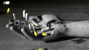 Mans hand falling holding pills after overdose in selective black and white