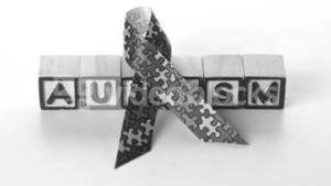 Awareness ribbon falling in front of autism letter blocks in black and white