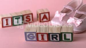 Its a girl message in letter blocks beside pink booties