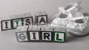 Its a girl message in letter blocks beside booties