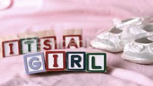 Its a girl message in letter blocks beside booties on pink blanket