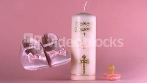 Baby shoes falling beside baptism candle and pacifier