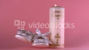 Baby shoes falling beside lit baptism candle