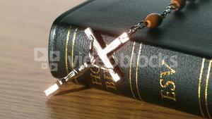 Rosary beads falling onto black bible