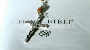 Rosary beads falling onto first page of bible