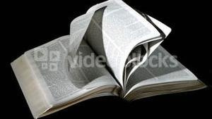 Bible pages turning in the wind on black background