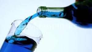 Blue liquid pouring into glass low angle close up