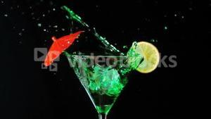 Ice falling into green cocktail