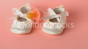 Pink soother falling onto baby shoes