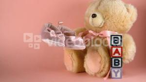 Baby shoes falling next to a teddy bear and baby blocks