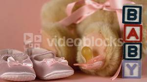 Pink soother falling besides baby shoes blocks and teddy bear