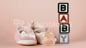 Pink soother falling in front of baby shoes and baby blocks