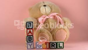 Teddy bear falling onto baby blocks and pink soother