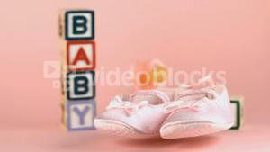 Baby shoes falling in front of baby blocks and soother