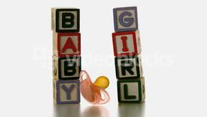 Yellow soother falling besides baby blocks