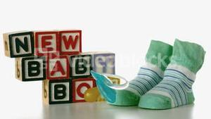 Blue soother falling besides slippers and baby blocks