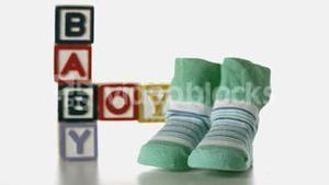 Slippers falling besides baby blocks on white background