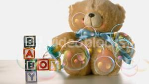 Bubbles floating over baby blocks soother and teddy bear