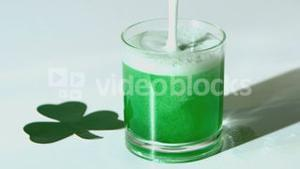 Green beer pouring into tumbler beside paper shamrock