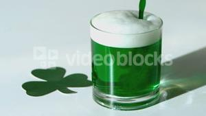 Green beer pouring into a tumbler beside paper shamrock