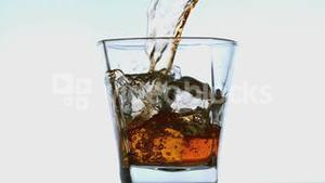 Whiskey pouring into tumbler with ice