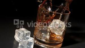 Ice cubes falling into tumbler of whiskey and ice